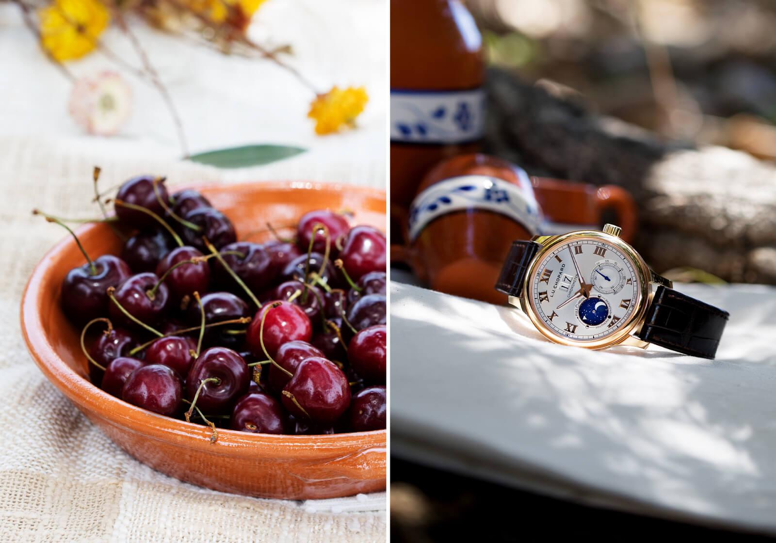 Taça com cerejas e Chopard L.U.C Lunar Big Date e ao fundo copos de barro.