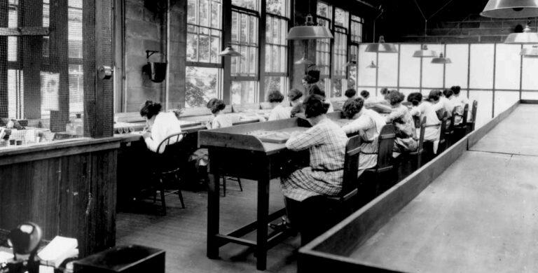 Jovens americanas sentadas a pintar mostradores com tinta à base de rádio.