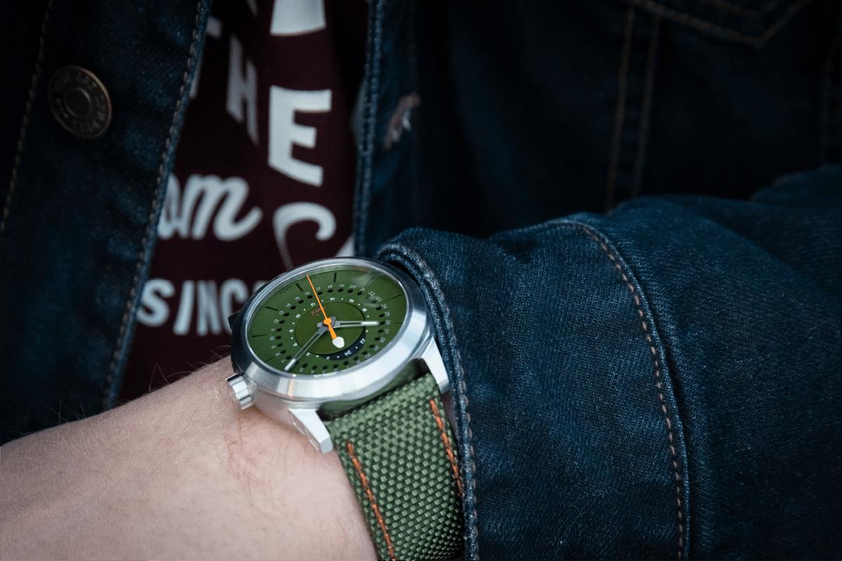 Isotope GMT 0º num pulso com casaco de ganga.