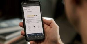 Mão com telemóvel onde se pode ver no ecrã a página do serviço online Breitling Select.
