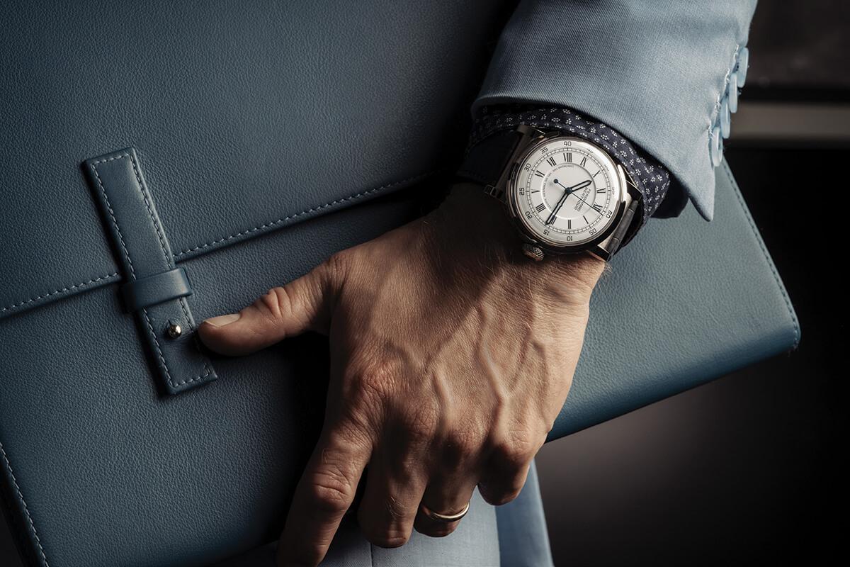 Chronomètre FB 2RE.1 num pulso masculino que segura uma pasta.