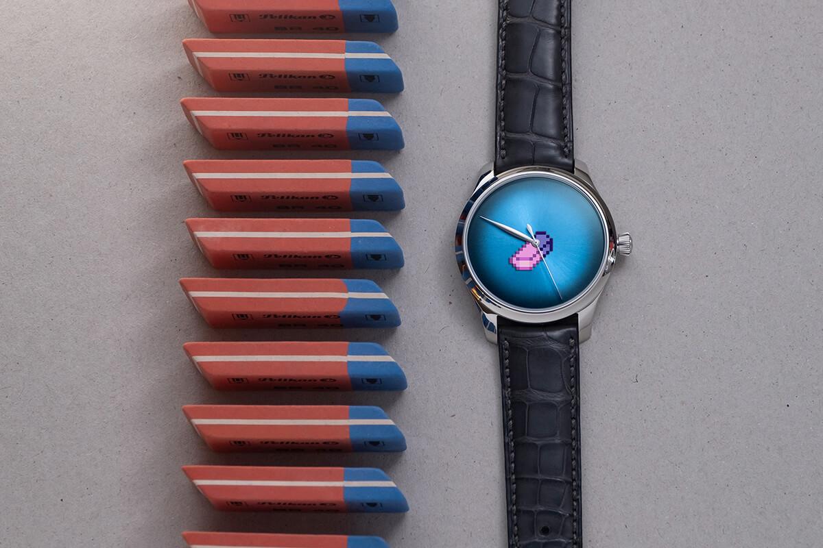 H. Moser & Cie. Endeavour Centre Seconds Concept X Seconde Seconde deitado de frente num fundo cinzento com borrachas azuis e vermelhas alinhadas ao lado