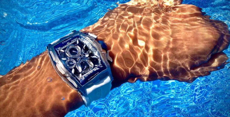 Cvstos Challenge Chrono II Power Reserve num pulso masculino debaixo de água num fundo azul