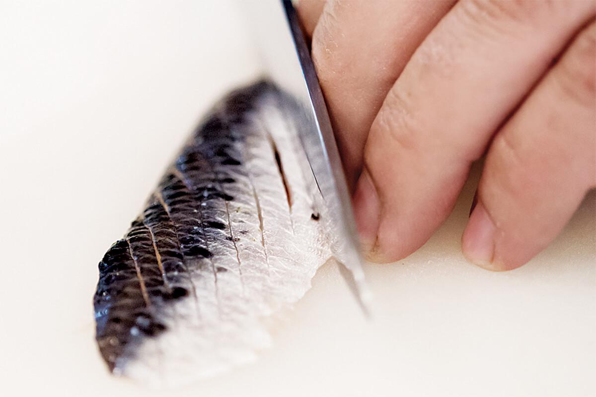 Imagem de uma faca a cortar uma sardinha em tiras finas. reparação do niguiri de sardinha no restaurante A Taberna do Mar