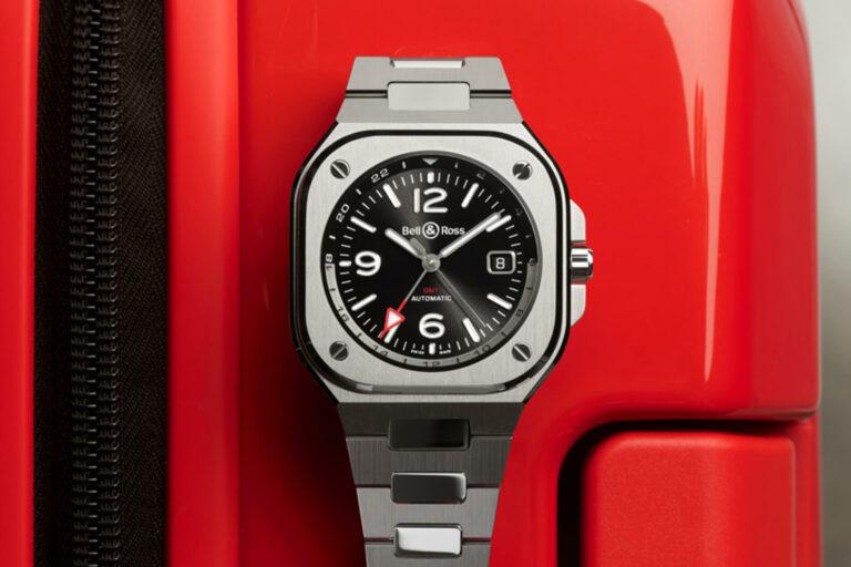 Bell & Ross BR05 GMT com bracelete em aço, com uma mala de viagem vermelho por trás.