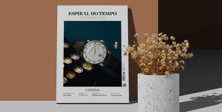 capa da Espiral do Tempo 76, edição de outono de 2021 cujo tema é Carisma, encostada a uma parede castanha com um vaso de flores secas em tons castanhos à sua direita